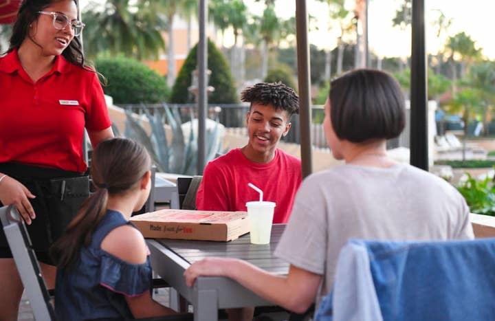 Family sitting outside looking at pizza box at Orange Lake Resort near Orlando, Florida