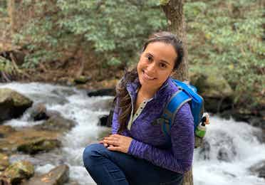 Featured author, Andrea Beltran, poses near a creek wearing a blue hiking backpack and purple pull-up sweater.