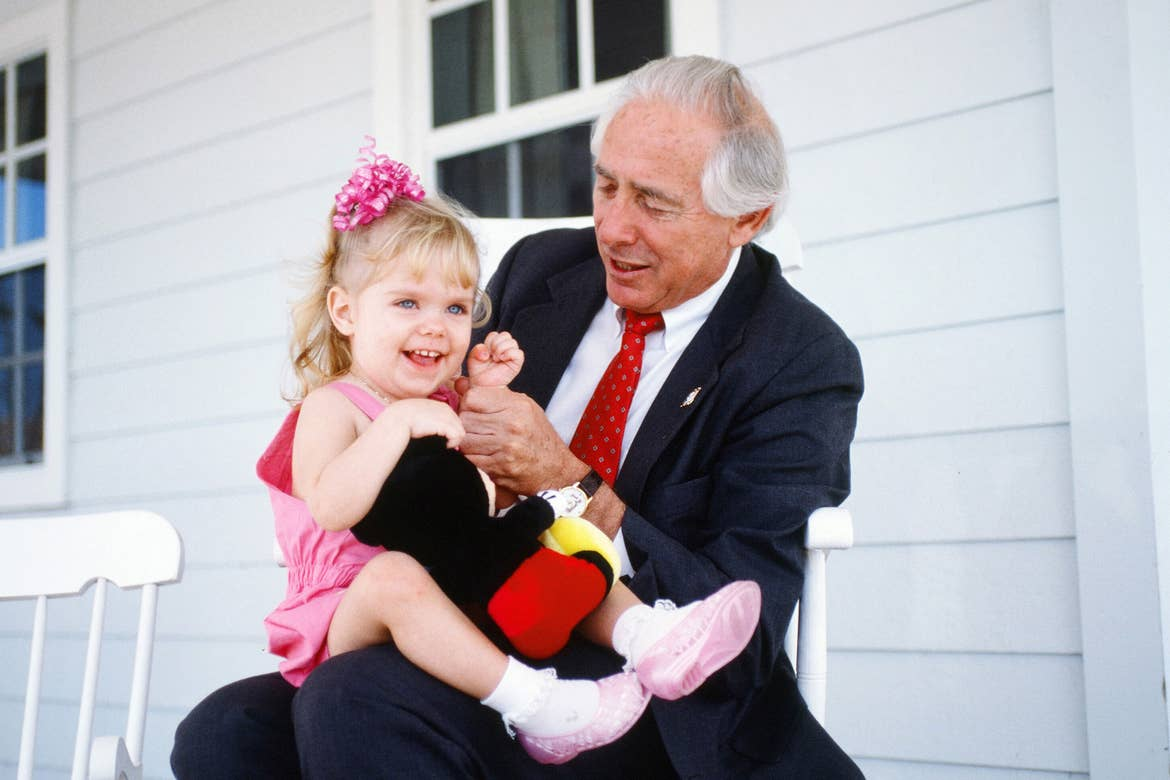 Founder of Give Kids the World Village, Henri Landwirth (right) holds a little girl (left) wearing a pink outfit and bow.