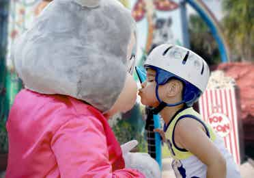 Boy wearing a helmet and giving a kiss to a bunny mascot