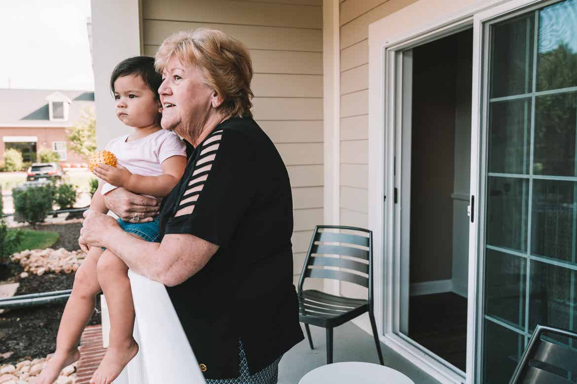 Featured Contributor, Angelica Kajiwara's mother holds Angelica's daughter outside on the patio at our Williamsburg resort in Williamsburg, Virginia.