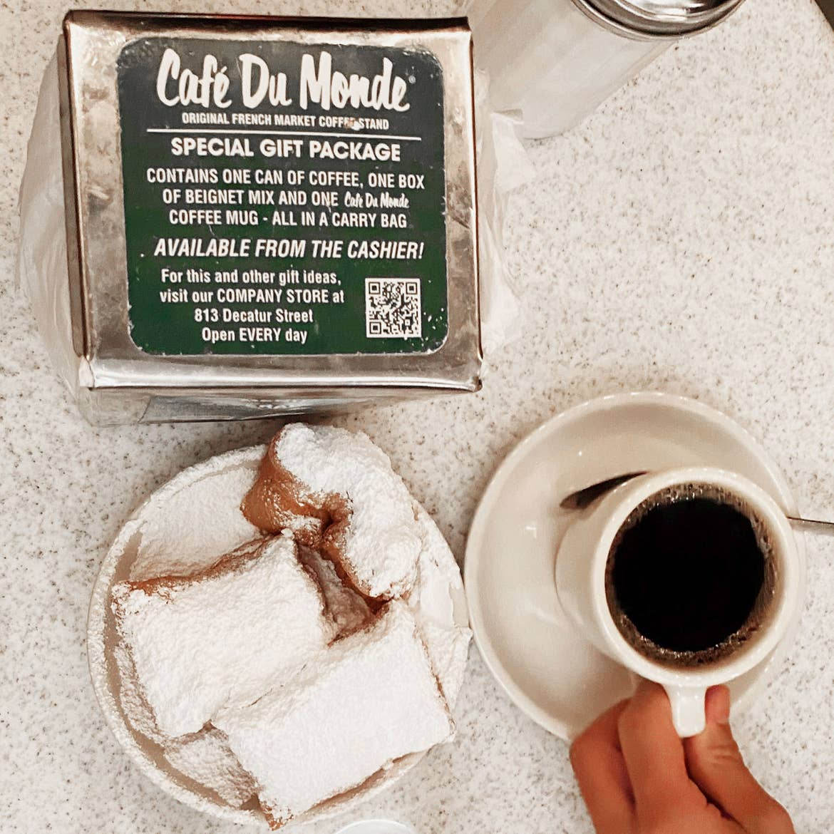 A Cafe Du Monde napkin box with beignets placed on a table with some coffee on white plates.
