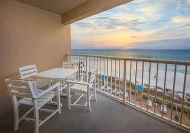 Furnished balcony with table and four chairs and view of ocean in a two-bedroom villa at Panama City Beach Resort