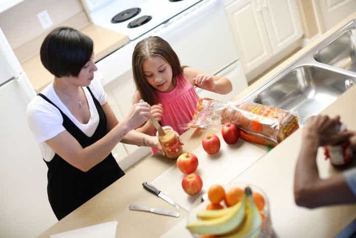 Clarissa Laskey (left) making PB&J picnic lunches at our Orange Lake Resort kitchen counter with her daughter (right.)