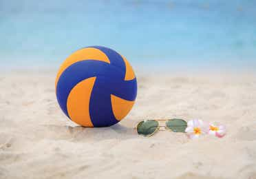 Beach volleyball and sunglasses laying in the sand beside the ocean