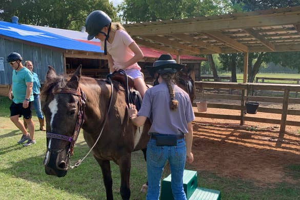 A caucasian girl (left) mounts a horse with the assistance of a handler.