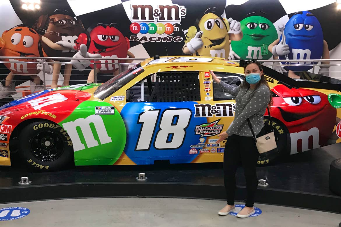 Featured Contributor, Ashley Fraboni, stands in front of a race car with m&m decals.