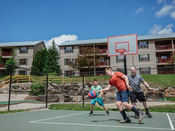 Dad and two sons playing basketball on outdoor sports courts at Oak n' Spruce Resort in South Lee, Massachusetts.