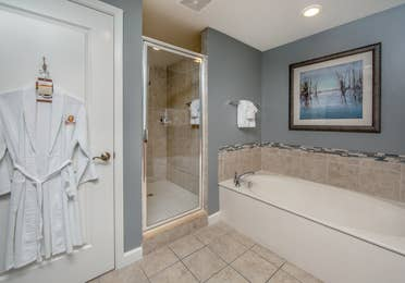 Bathroom with walk-in shower, bathtub, and robe in a three-bedroom villa at Sunset Cove Resort in Marco Island, Florida