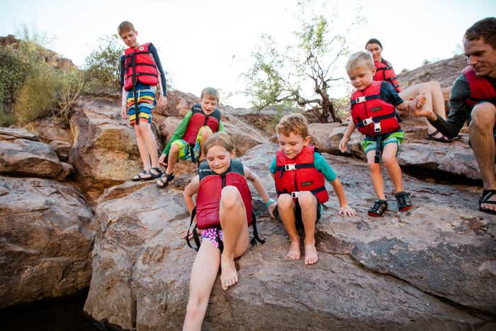 The Averett family wearing their life jackets on a cliff near the edge of the lake.