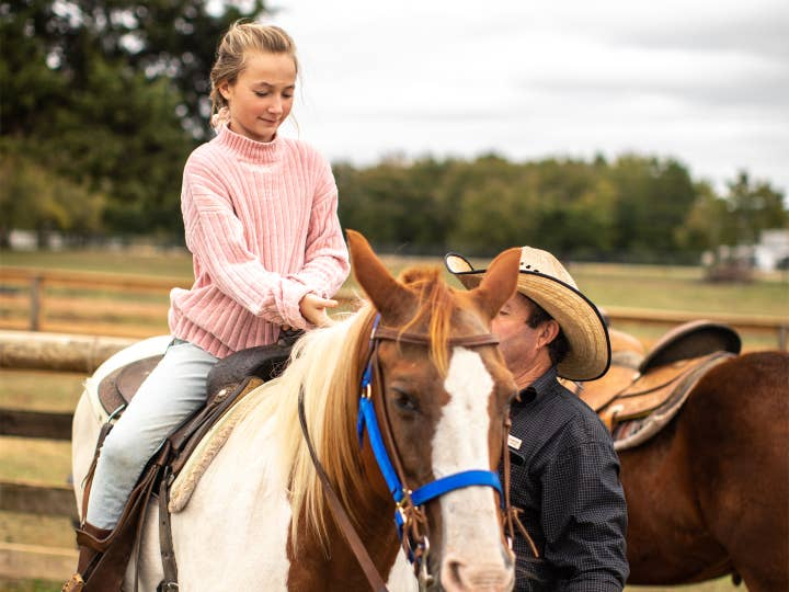 Child sitting on horse with adult supervising at Villages Resort in Flint, Texas.