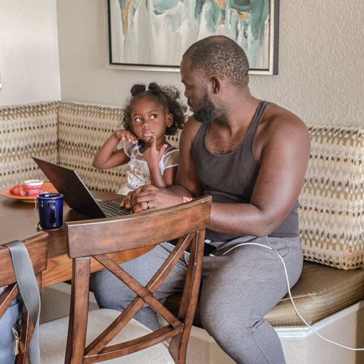 Author, Kimberly Gelin's daughter (left), sits on her dad's (right) lap at the dining table in our Villa at Orange Lake Resort in Florida with her laptop for virtual learning.