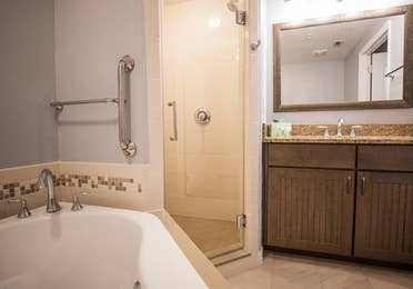 Bathroom with a tub and walk-in shower in a two-bedroom villa at Cape Canaveral Beach Resort.