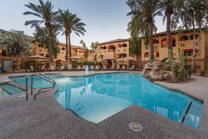 A view of the pool at Scottsdale Resort with villa buildings and palm trees in the background.