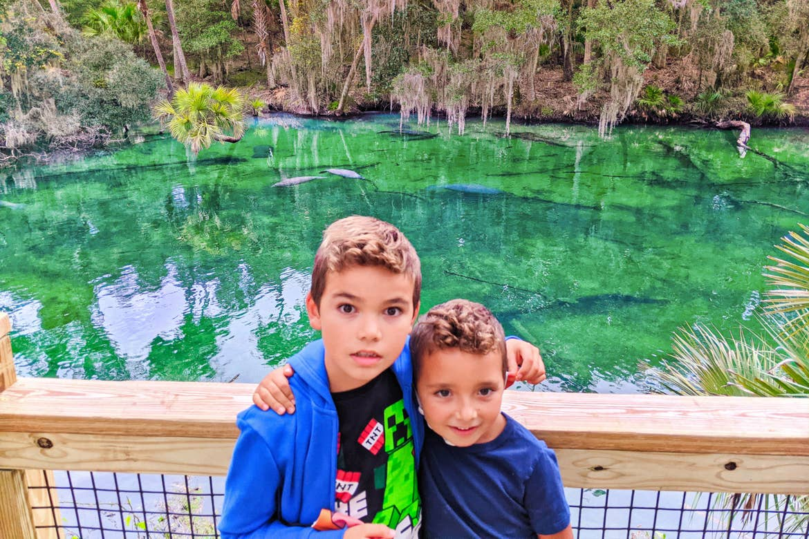 Two young boys, one with a blue hoodie and the other with a blue long-sleeve t-shirt, stand on a wooden bridge where crystal clear waters filled with manatees and fauna at Blue Spring State Park in Florida.