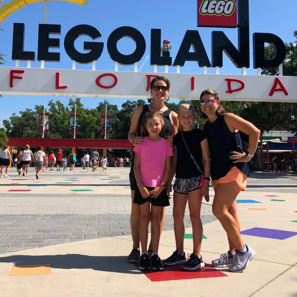 Two women (back) and two young girls (front) stand in front of a LEGOLAND sign in Orlando.