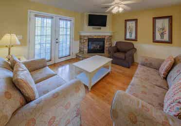 Living room with two couches, an accent chair, flat screen TV, and fireplace in a presidential two bedroom villa at Piney Shores Resort in Conroe, Texas