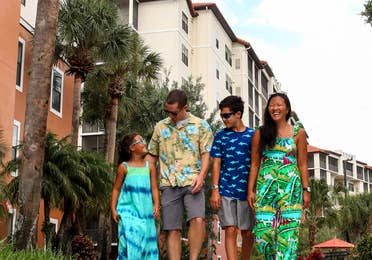 A biracial family of four walk on a path near the exterior of our Orange Lake Resort located in Orlando, Florida.