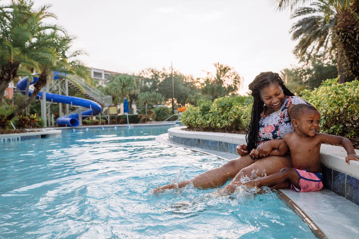 Featured Contributor, Krystin Godfrey (left) and her son (right) sit along the edge of our zero entry pool in River Island at our Orange Lake resort located in Orlando, FL.