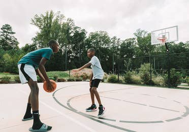 Two teens playing basketball on an outdoor court