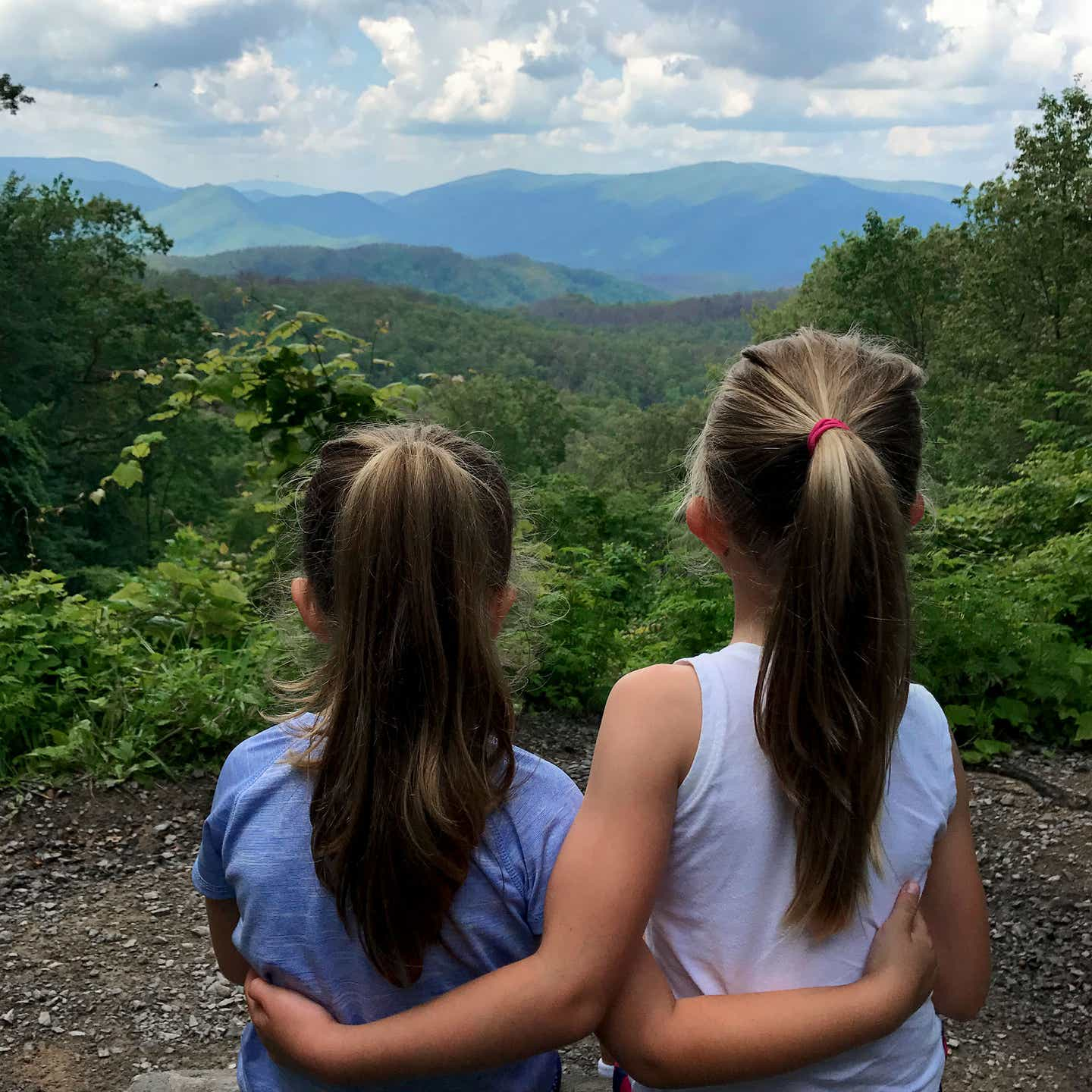 Author, Chris Johnstons' daughters, Kyndall (right), and Kyler (left) face out to the trees of the Great Smoky Mountains while wrapping one arm around each other.