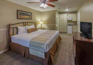 Bed in a  two-bedroom lock-off with a view of the kitchenette at Villages Resort
