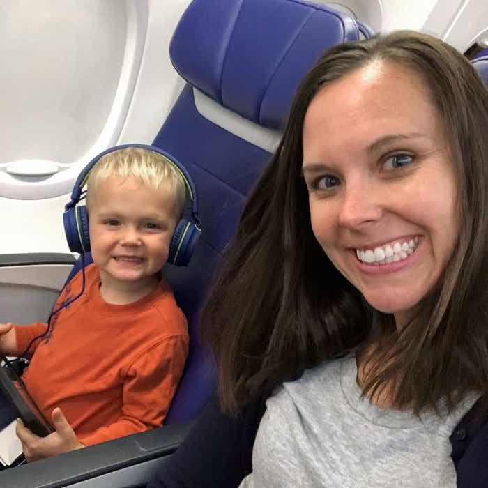 Author, Sarah, and son, Logan, sit near the window seat on their airplane pre-COVID.