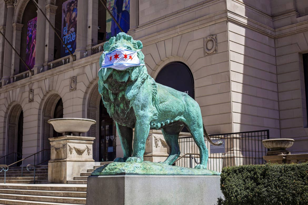A lion statue wears a Chicago-flag safety mask outside of the Art Institute of Chicago.