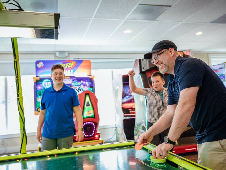 Dad and children playing air hockey at Oak n' Spruce Resort in South Lee, Massachusetts.