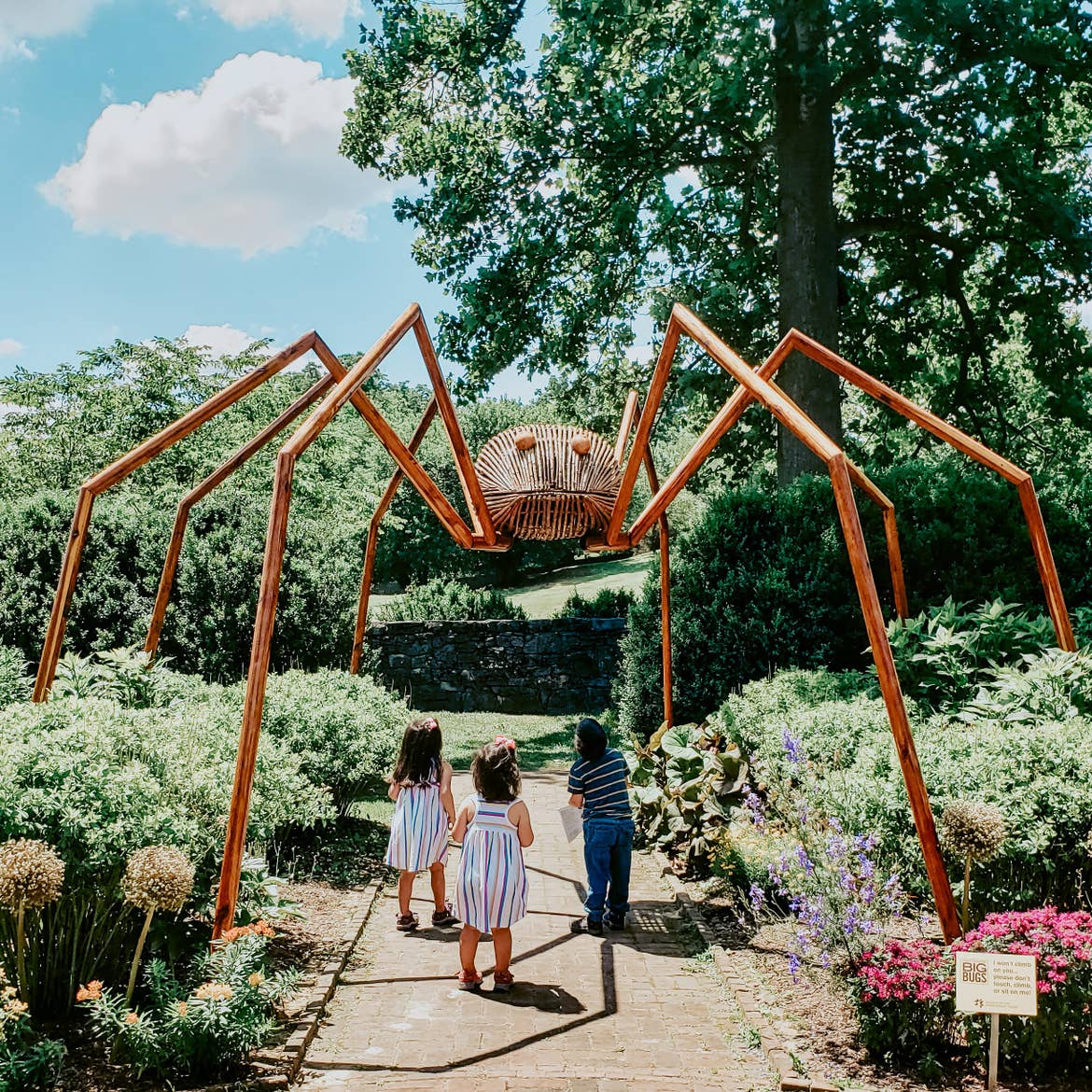 Angelica's kids looking up at a giant wooden spider at the Big Bugs Sculpture Exhibit at the Museum of the Shenandoah Valley.