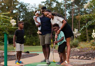 Family at a miniature golf course as a mother helps her son swing the club.