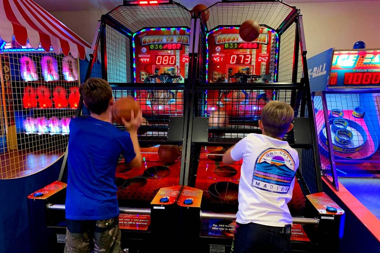 Two boys play a basketball arcade game.