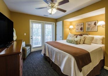 Bedroom with TV in a three-bedroom ambassador villa at the Holiday Hills Resort in Branson Missouri.