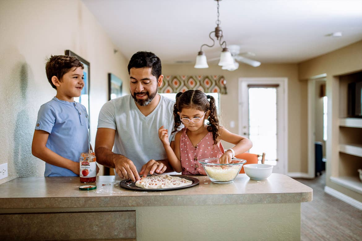 A man (middle), a young boy (left) and girl (right) prepare a pizza at a countertop in a villa.