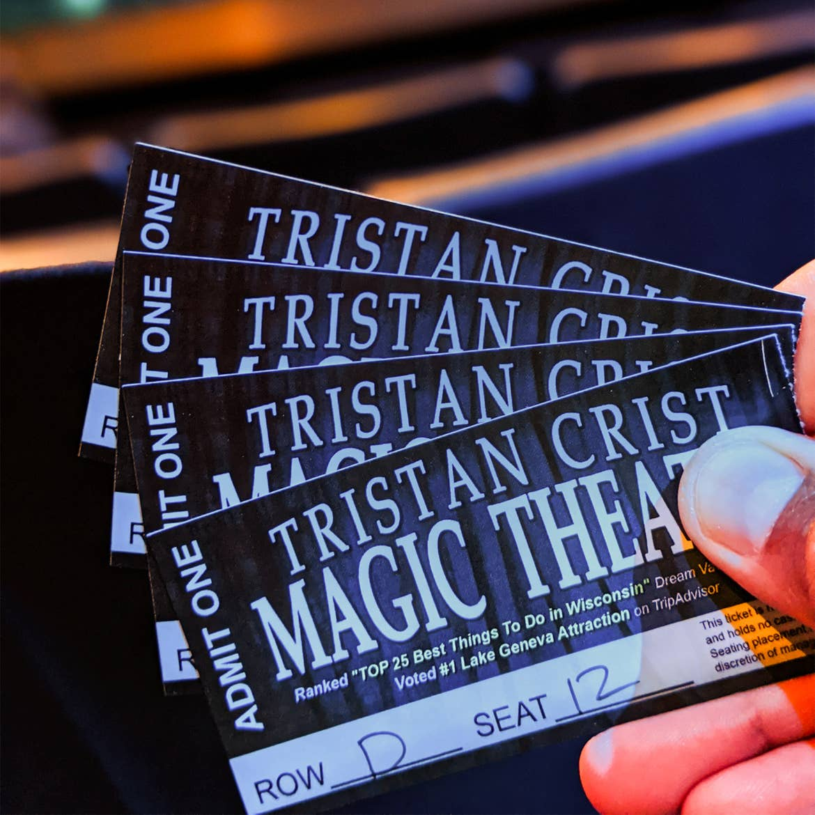 A hand holding tickets.
