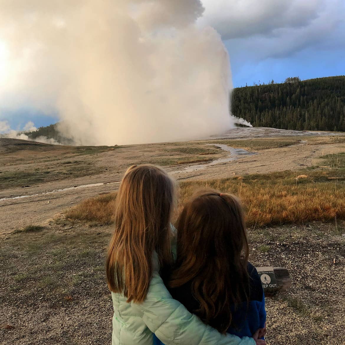 Author, Chris Johnstons' daughters, Kyndall (left), and Kyler (right) face out to watch Old Faithful at dusk while wrapping one arm around each other.