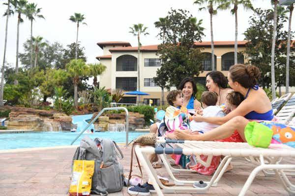 Family sitting on lounge chairs around the pool at Orange Lake Resort in Orlando, FL