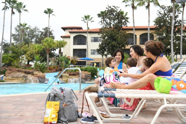 Family sitting on lounge chairs around the pool at Orange Lake Resort in Orlando, FL