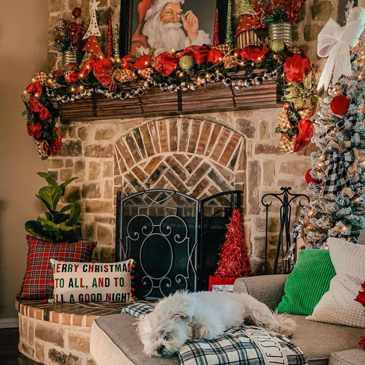 A small 'pencil tree' decked out in holiday decor next to a mantle decked out in holiday decor.