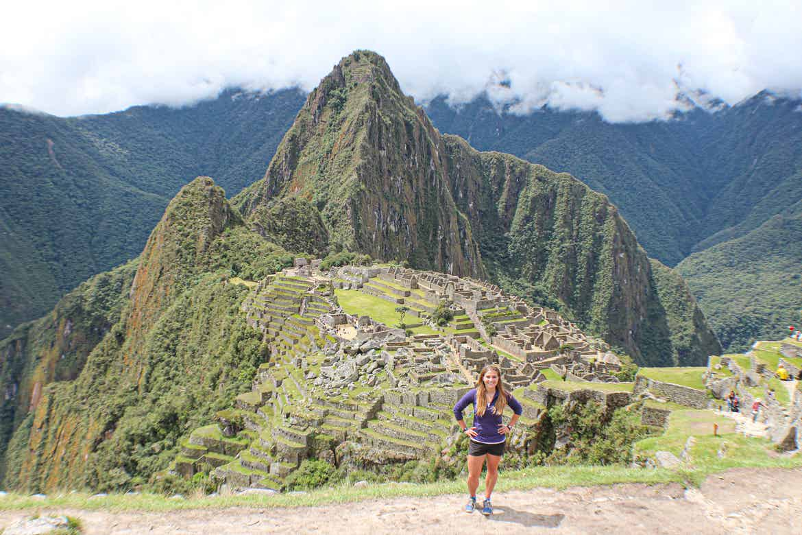 Featured Contributor, Ashlyn George, stands in front of the ruins of an ancient mountain village in Peru.