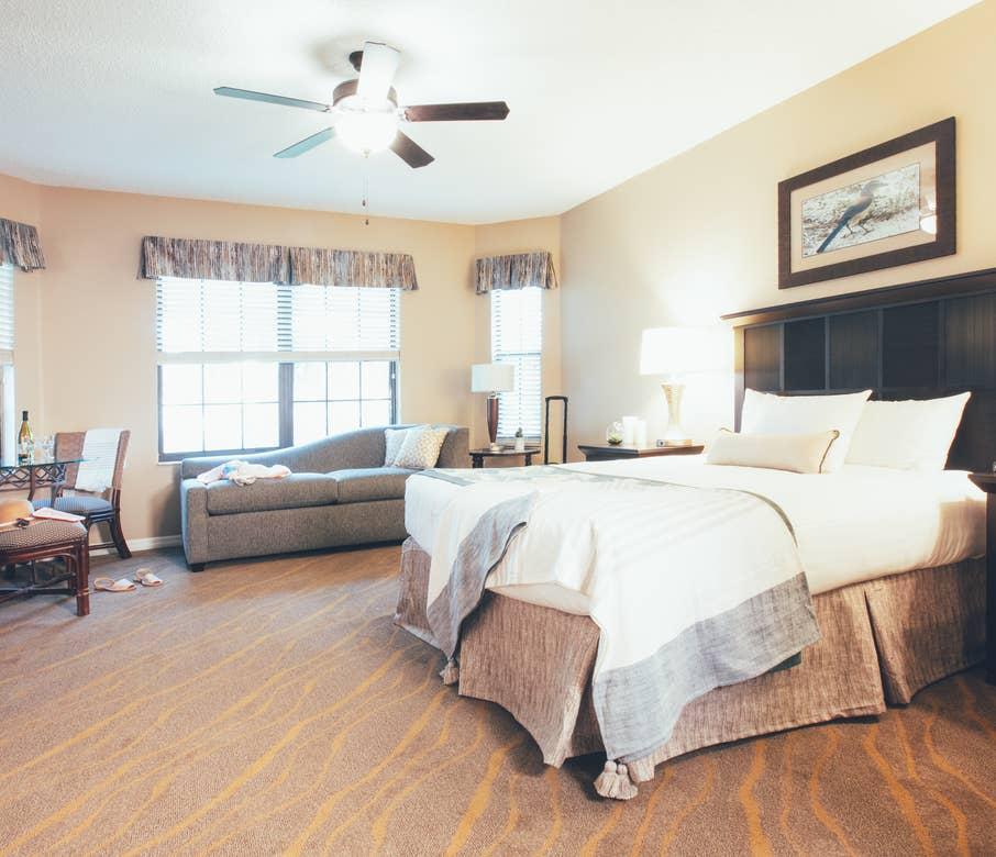 Bedroom with seating area and three windows in a three bedroom villa in North Village at Orange Lake Resort near Orlando, Florida