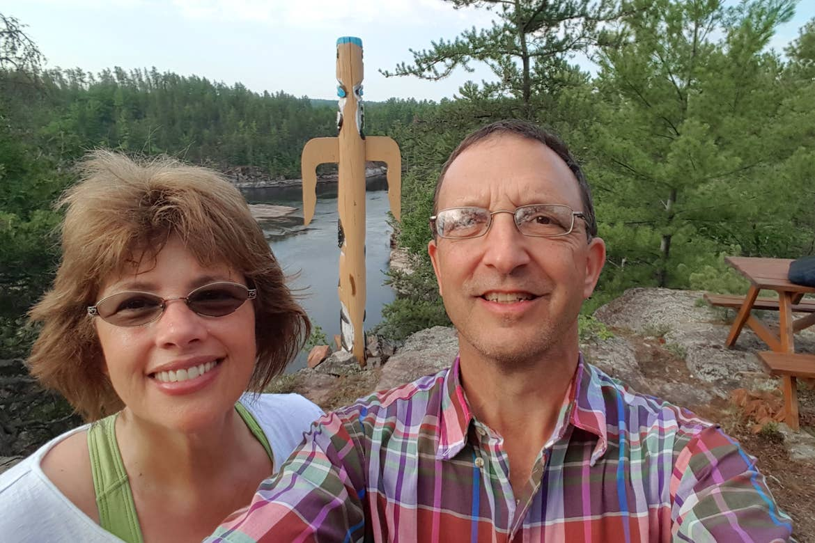 a caucasian woman wearing a green camisole under a white t-shirt (left)n and a caucasian man wearing a plaid button-up shirt (right) stand near a totem at the Dokis First Nation Reservation in Ontario, Canada.