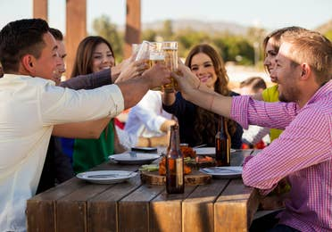 Group of young people toasting with glasses of white wine while dining outdoors
