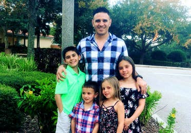 Featured Member, Sara Perezes husband poses with their four children outdoors.
