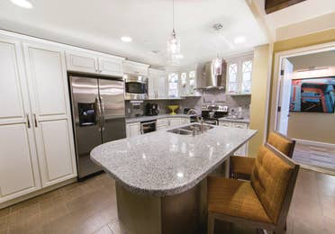 Full kitchen with large island and stainless steel fridge, oven, microwave, sink, and large pantry in a Signature two-bedroom villa at Galveston Beach Resort