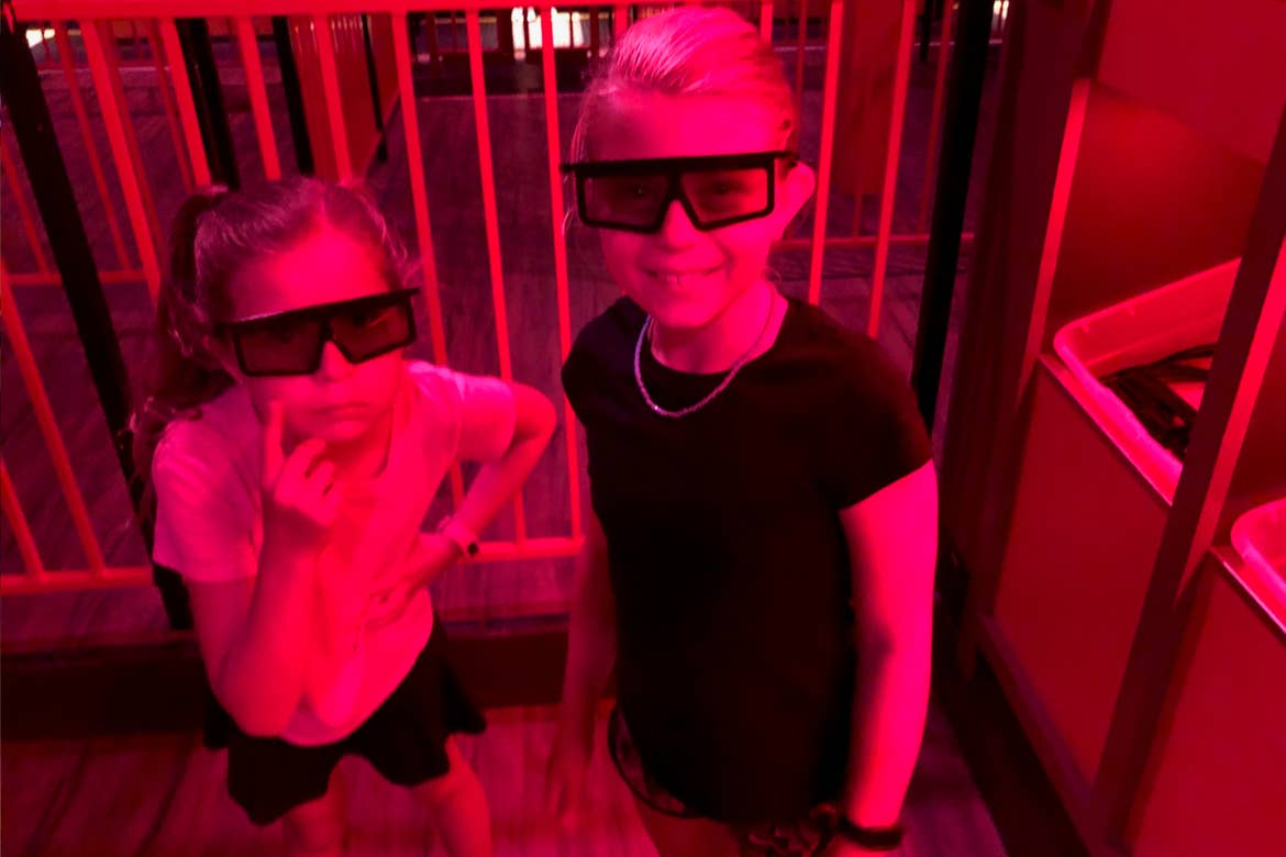 Two young girls stand in a queue wearing 3D glasses.