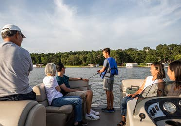 Family of six sitting on pontoon boat while child fishes at Villages Resort in Flint, Texas.