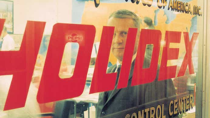 Kemmons Wilson standing behind a window with the Holidex logo