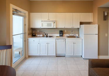 Kitchen with fridge, microwave, dishwasher, and stovetop in a two-bedroom villa at Galveston Beach Resort
