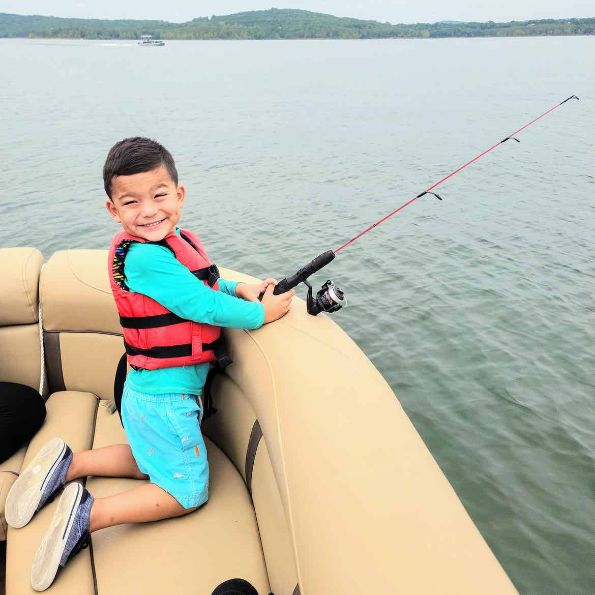 Angelica's son goes fishing off the side of a tritoon wearing a life jacket and aqua swimwear.